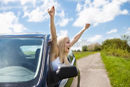 frau hebt hand aus autofenster