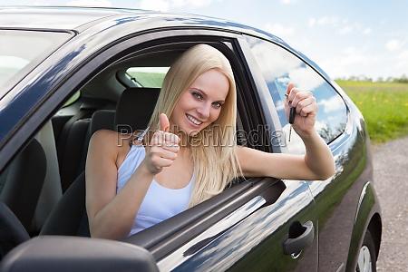 glueckliche frau in einem auto zeigen