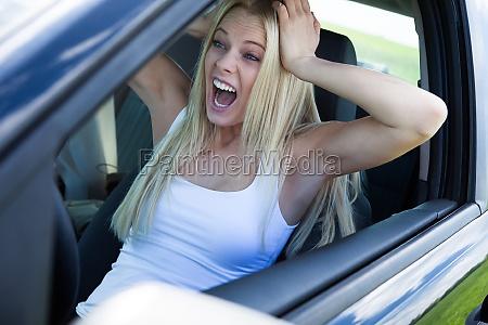 blonde frau sitzt im auto und