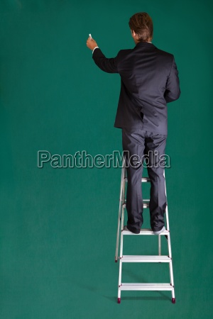 businessman standing on ladder writing on