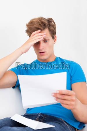 shocked man holding paper