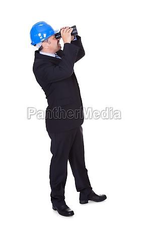 male architect looking through binoculars