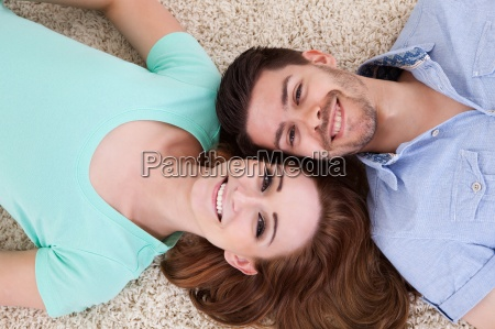 happy young couple lying on back