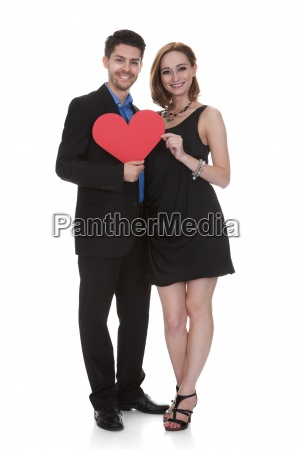 young couple holding paper heart