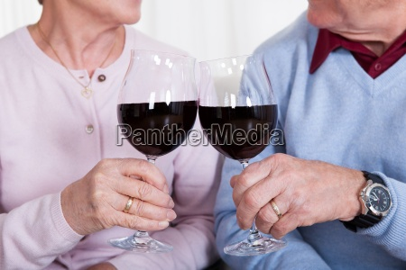 senior couple toasting glass of wine