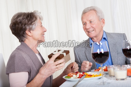 senior man giving gift to senior