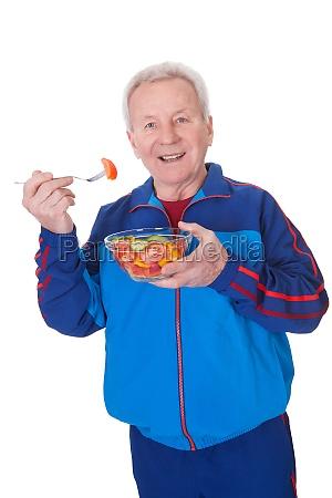 senior man eating salad