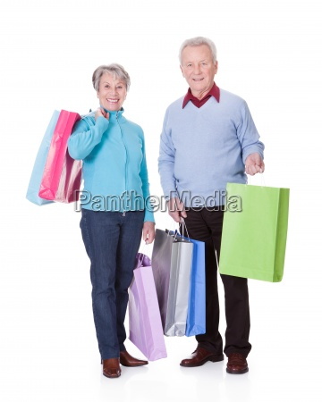 senior couple holding einkaufstaschen
