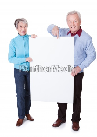 senior couple holding blank placard