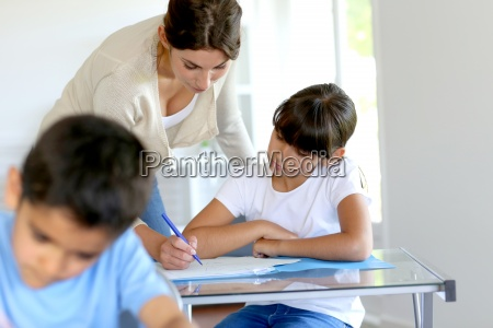 teacher helping young girl in class
