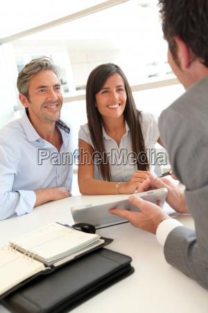 immobilienmakler hausplaene auf elektronischen tablet zeigt