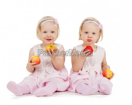 zwei identische zwillingsmaedchen mit aepfeln spielen