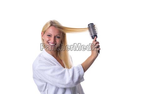 blondine mit haarbuerste in der hand