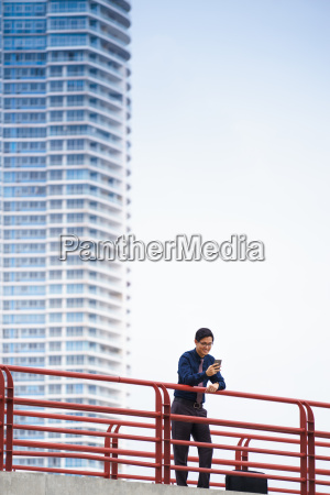 portrait asian office worker texting mobile