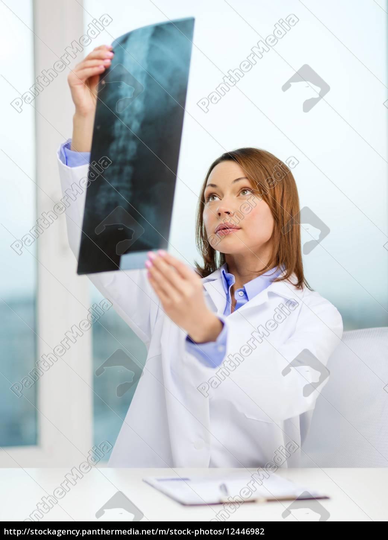 konzentrierter, arzt, mit, blick, auf, röntgenaufnahmen - 12446982