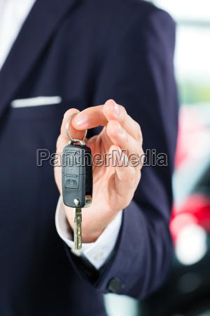 seller with car in car dealership