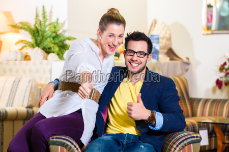 couple buying armchair in furniture store