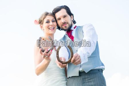 brautpaar mit hufeisen als glueckssymbol