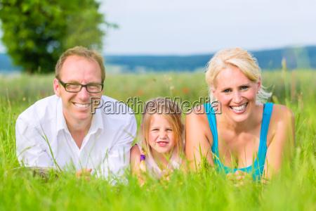 familie liegt im grass auf feld