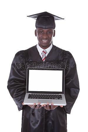 absolventen mann zeigt laptop