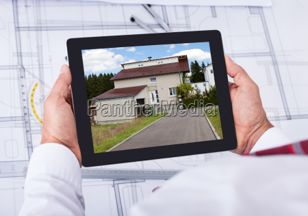 male architect holding digital tablet over
