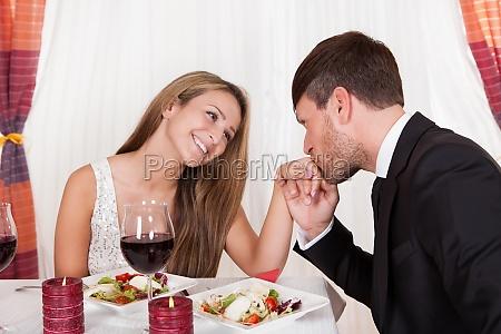 man kissing a womans hand at