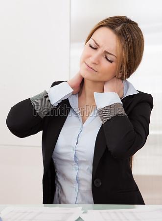 junge attraktive geschaeftsfrau leiden unter nackenschmerzen