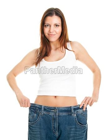 schlanke frau zieht uebergrosse jeans