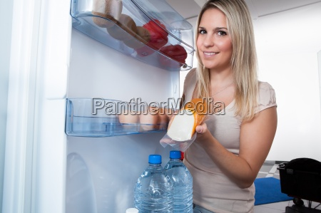 woman taking sausage from refrigerator