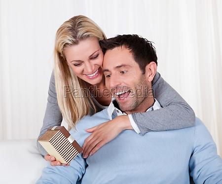 frau die ihren mann ein ueberraschungsgeschenk