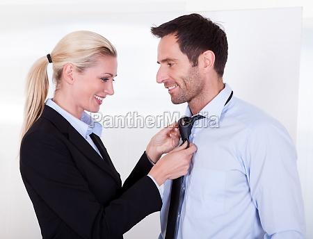 businesswoman putting tie on businessman