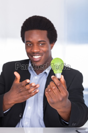 businessman holding light bulb with green