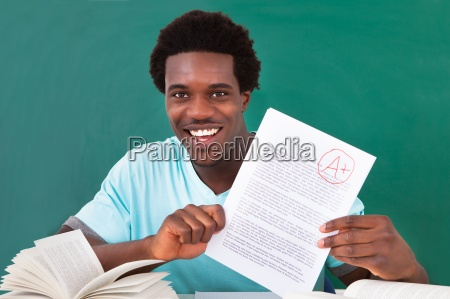 young man showing a paper with