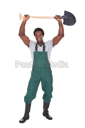 male gardener holding shovel
