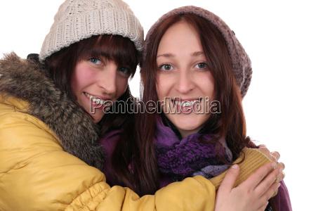 zwei junge frauen im winter umarmen