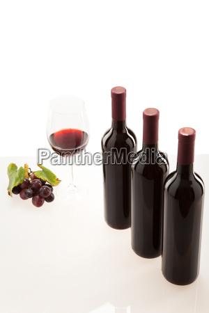 rotwein im glas mit frucht blaetter