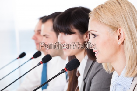 geschaeftsleute sprechen in mikrofon
