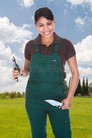 female gardener holding gardening tools