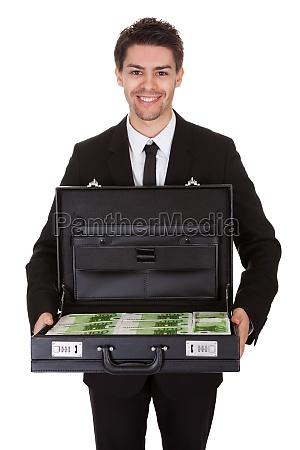 geschaeftsmann mit koffer voller bargeld