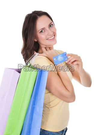 woman with shopping bags holding credit