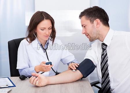 junger doktor der blutdruck ueberprueft