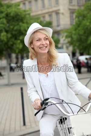froehlich frau mittleren alters fahrrad fahren