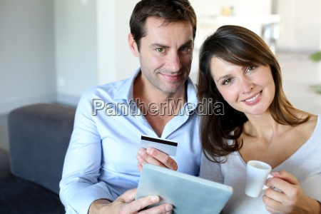 mature couple at home using credit