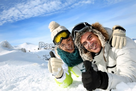 couple of skiers laying down in