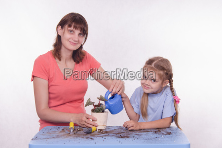 mom and daughter watering potted flower