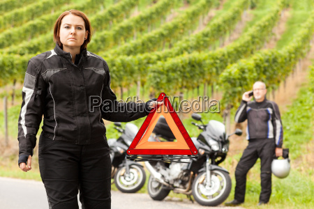 motorcyclist with warning triangle in case