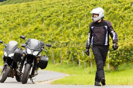 motorradfahrer mit helm geht auf der
