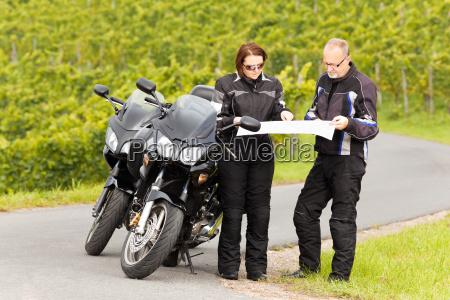 zwei motorradfahrer blicken auf die strassenkarte