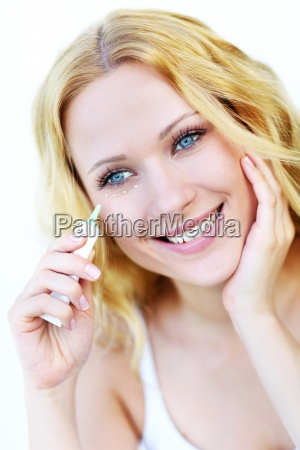 smiling woman applying concealer in front
