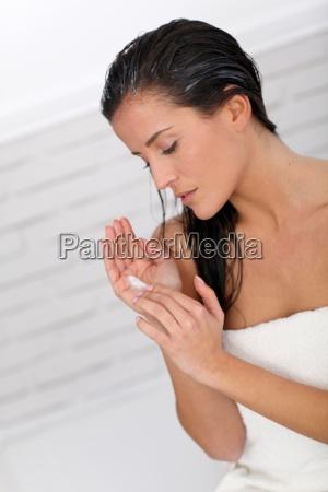 mujer hermosa que aplica el acondicionador